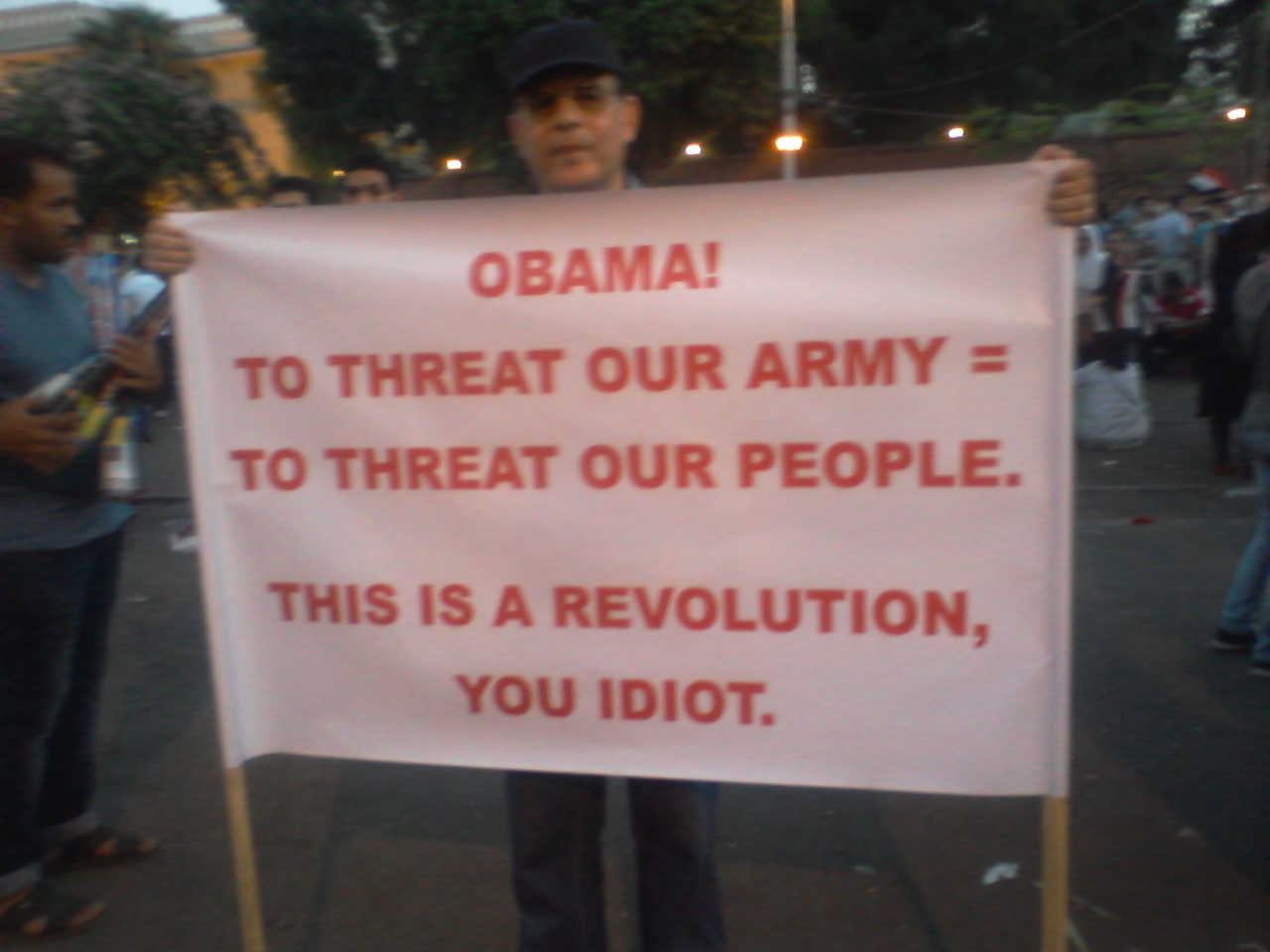 Egyptian protester holding a sign that reads To Threat our Army = To Threat our People