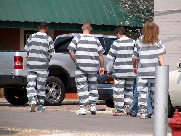 People in Prison Jump Suits Walking with Ankles in Chains